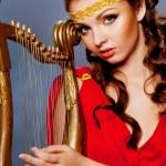 Beautiful young girl playing the harp — Stock Photo #55034775