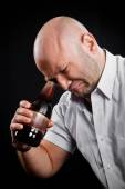 Man very emotionally looks at the bottom of the bottle — Stock Photo