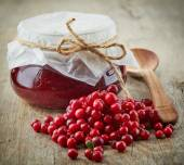 Fresh raw cowberries and jar of jam — Stock Photo