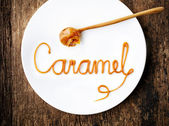 Word Caramel on white plate — Stock Photo