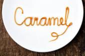 Word Caramel on white plate — Stock Photo