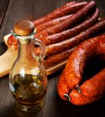 Bottle of olive oil and smoked sausage on a rural table — Stock Photo