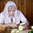 The old woman cuts  vegetable marrow on a table — Stock Photo #75626995