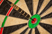 Dart in bulls eye close up — Stock fotografie