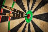 Three darts in bulls eye close up — Stock Photo