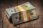 Stacks of 100 dollars banknotes bundles — Stock Photo