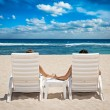 Couple in beach chairs holding hands near ocean — Stock Photo #59363861
