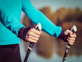 Womans hand holding nordic walking poles — Stock Photo
