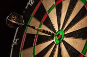 Dart in bulls eye close up — Stock Photo
