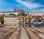 Wooden planks vith view of Prague Charles bridge over Vltava riv — Stockfoto