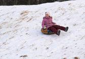 Happy teenage girl sliding down on snow tube — Stock Photo