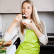 housewife in apron eating cottage cheese   — Stock Photo #52528309