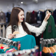 Woman choosing sweater at clothing store — Stock Photo #52529765