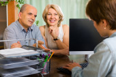Public notary helping happy aged couple to make a will — Stock Photo