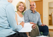 Mature couple discussing  private insurance with agent — Stock Photo