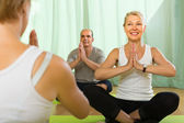 Mature couple practicing yoga with instructor — Stock Photo