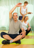 Mature couple with trainer at gym — Stock Photo