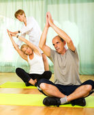 Yoga instructor showing asana to mature couple — Stock Photo