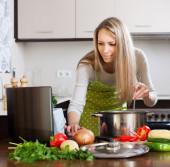 Femme à l'aide de portable tout en faisant cuire la soupe — Photo