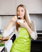 housewife in apron eating cottage cheese   — Stock Photo