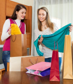 Happy girls looking purchases from  bags — Stock Photo