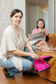 Clean up woman, while mature mother reads newspaper — Stock Photo