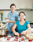 Smiling women making  pies with berries  — Stock Photo