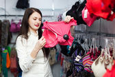 Smiling woman choosing bra at store — Стоковое фото