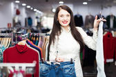 Girl choosing trousers at boutique — Stock Photo