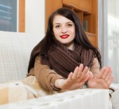 Woman in scarf  warming near warm heater  — Stock Photo