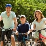 Happy family of three cycling through city — Stock Photo #52533071