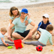 Parents with children playing in the sand — Stock Photo #52533199