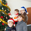Happy family of four with Christmas tree — Stock Photo #52534761