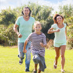 Happy family of three running on grass — Stock Photo #52535335
