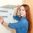 Long-haired smiling woman turning off the light-switch — Stock Photo