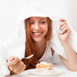 Woman eating sweet cake under sheet in bed — Stock Photo #52536501
