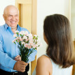 Senior man giving flowers to woman — Stock Photo #52537347
