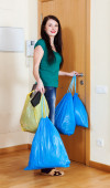 woman near door with garbage bags  — Stock Photo