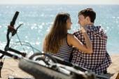 Girl and her boyfriend  on beach near bikes — Stock Photo