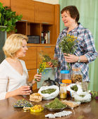 Two women brewing herbal tea — Stock Photo