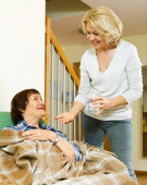 Elderly woman offering pills and water to pensioner — Stock Photo