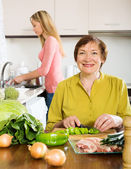 Happy mature woman with adult daughter cooking  together  — Stock Photo
