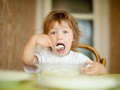 Kind eet zuivelproducten met lepel — Stockfoto