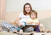 Zwangere vrouw en dochter leest boek — Stockfoto