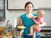 Happy woman with baby  cooking mashed potatoes  — Stock Photo