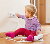 Toddler playing with extension cord and outlet   — Stock Photo