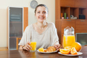 Happy  woman having breakfast with croissants — Stockfoto