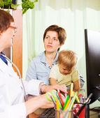 Mother with baby listening friendly  doctor   — Stock Photo