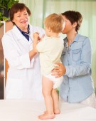 mature  doctor examing baby  at clinic — Stock Photo