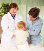 Happy   pediatrician doctor examining toddler   — Stock Photo
